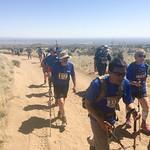 The BVA crew hikes uphill on the sandy road.  A desert mountain range spans the horizon.