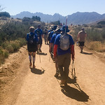 The BVA crew hikes away from the camera, uphill on the sandy road.  A desert mountain range spans the horizon.